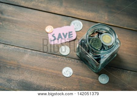 Coins in glass jar with the word save in background. Photo with vintage tone. Saving money concept.