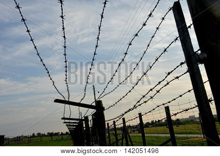Barb-wire fence against sombre sky and green grass background. Majdanek or KL Lublin concentration and extermination camp established on the outskirts of the city of Lublin during the German occupation of Poland in World War II.