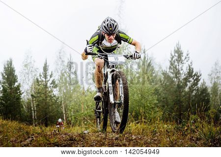 Revda Russia - July 31 2016: race leader male athlete mountainbiker during Regional competitions on cross-country bike