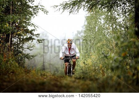 Revda Russia - July 31 2016: elderly male athlete mountainbiker rides in forest during Regional competitions on cross-country bike