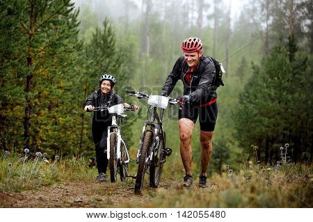 Revda Russia - July 31 2016: young couple of cyclists go uphill with your mountainbike during Regional competitions on cross-country bike
