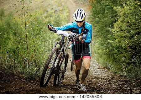 Revda Russia - July 31 2016: young girl mountainbiker climb mountain on foot with their bikes during Regional competitions on cross-country bike