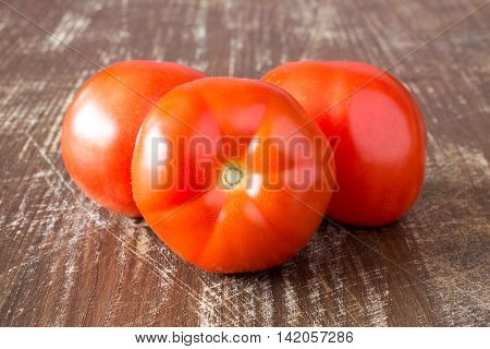 Three red tomatoes on a wooden background.