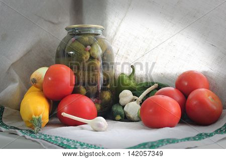 Canned vegetables - Bank of canned cucumbers on a background of tomatoes peppers zucchini garlic and other vegetables