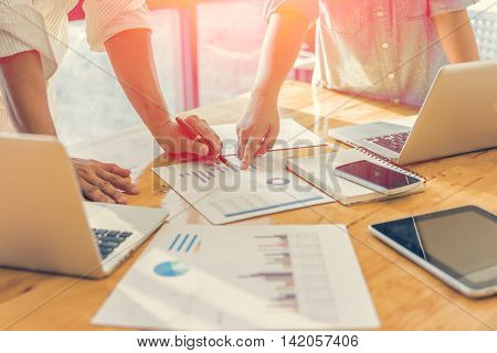 Business people analyzing investment charts. Accounting with soft focus vintage tone