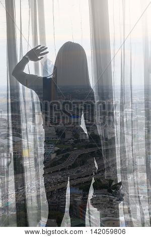 double exposure and de-focused Woman stand near window and hold white bouquet flowers with townscape background