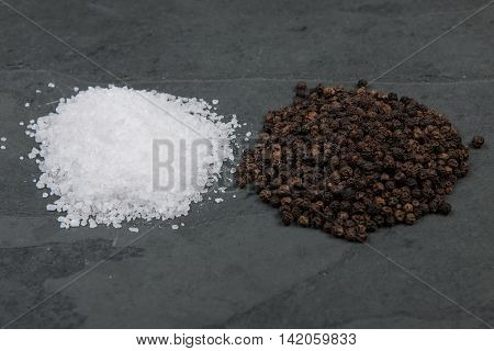 Pile of salt and pepper on grey slate table stock picture