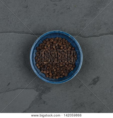 Small bowl of pepper corns on a grey slate table