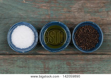 Salt pepper and oil on a wooden table stock picture
