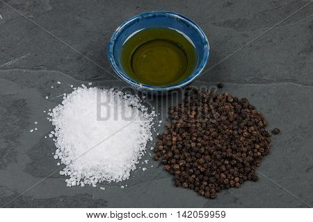Salt pepper and oil on a grwy slate table
