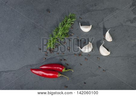 Dill red peppers black pepper corn and garlic on a grey slate plate stock picture