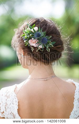 Romantic hairstyle with fresh pink and blue flowers