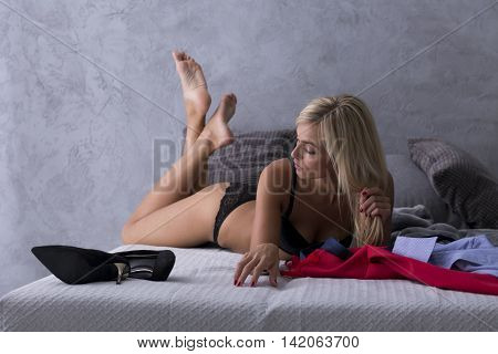 Beautiful blonde woman in a sexy black underwear lying on a hotel bed