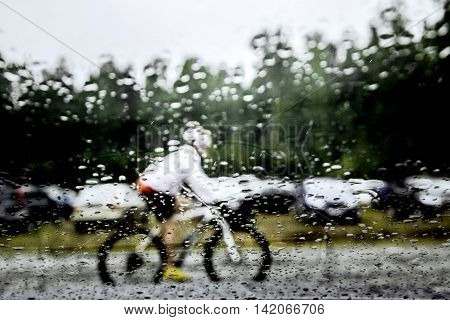 blurry image behind glass in rain athlete mountainbiker riding on street