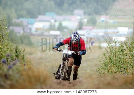 athlete mountainbikers climb mountain on foot with bicycle during competitions in cross-country