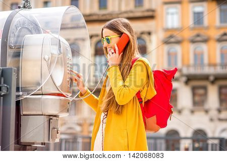 Young woman in yellow sweater and backpack calling with city call box in the old italian town.
