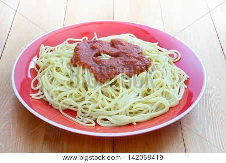 Marinara topping over freshly cooked spaghetti pasta in round ceramic plate on smooth wooden table