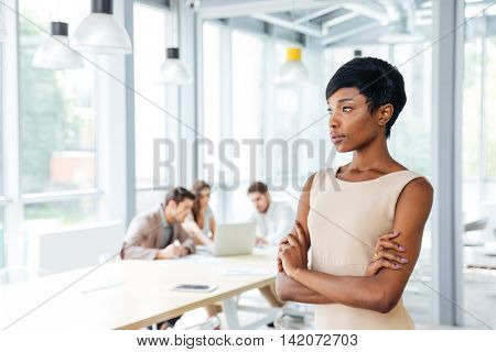 Pensive african american young businesswoman standing with arms crossed and thinking in office