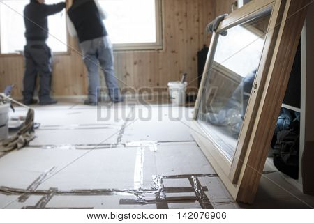 Workers in the background installing new three pane wooden windows in an old wooden house with a new window in the foreground. Home renovation sustainable living energy efficiency concept.