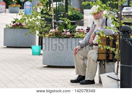 IMATRA FINLAND June 24: The old man has a rest sitting on a bench on a hot summer day in the streets of the Finnish town of Imatra 24 June 2016.
