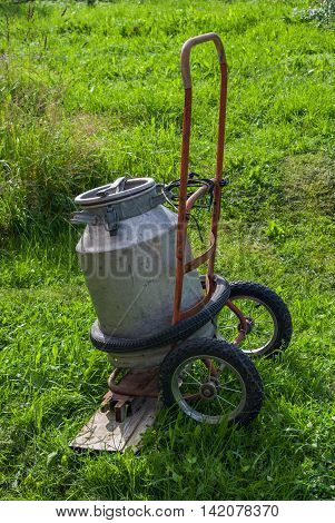 Old aluminum cans on old hand truck on a background of green grass.