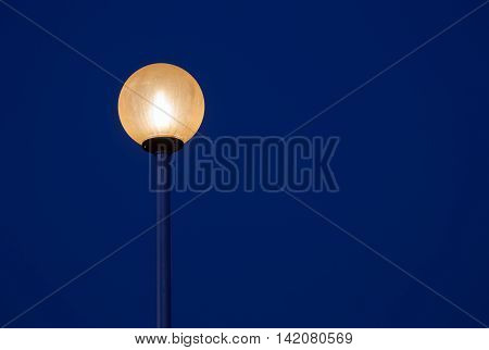 Round glowing streetlight on dark blue sky