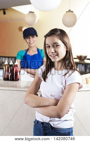Girl And Waitress Standing Arms Crossed At Ice Cream Parlor