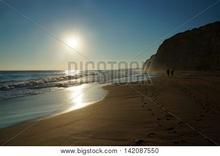 A couple - black silhouettes in front of the setting sun - strolls along the water's edge at high tide leaving two lines of foot prints leading down the beach. The sun is reflected on the water and on the wet sand. Algarve, Portugal.