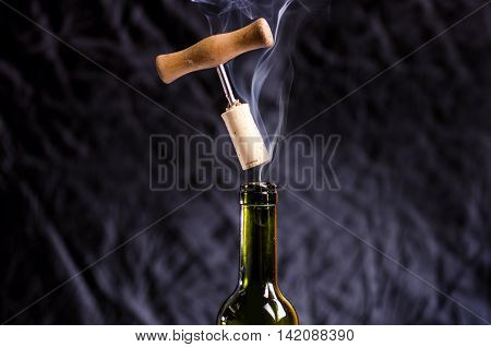 Opening a wine bottle with a corkscrew on a white background. Wine bottle with steam. Levitation of corkscrew. Isolated.