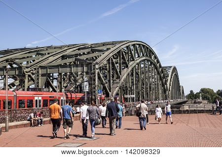 COLOGNE GERMANY - AUG 7 2016: People walking at the Hohenzollern Bridge in Cologne North Rhine-Westphalia Germany