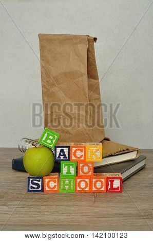 The words back to school spelled with colorful alphabet blocks displayed with a green apple. a paper lunch bag and a stack of books on a table with a white background