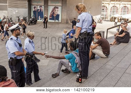 COLOGNE GERMANY - AUG 7 2016: Policewomen and a policeman checking pasport of a drunk refugee in front of the central station in Cologne Germany
