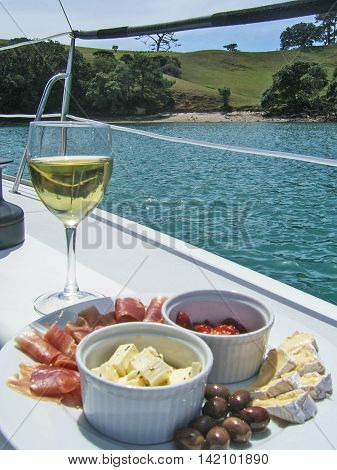 White wine and an antipasto platter with cheese prosciutto olives and sundried tomatoes on deck of sailing yacht in New Zealand NZ.