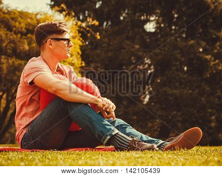 Love romance sadness heartbreak concept. Young man resting in park. Sad boy sitting with heart.