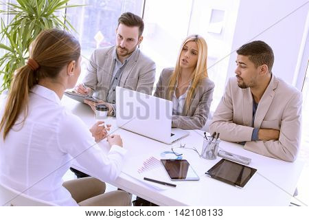 Group of business people having job interview.They are communicating with female candidate.