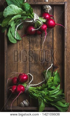 Fresh radish banches on wooden tray background. Top view, copy space, vertical