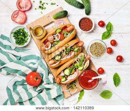 Homemade hot-dogs on wooden serving board with fresh vegetables, spices, ketchup and mustard over white painted old wooden background, top view