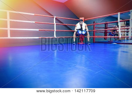 Male boxer with towel resting in the corner of the boxing ring
