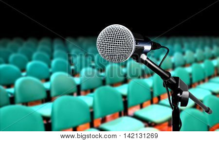 Microphone in auditorium during seminar presentation with green seats