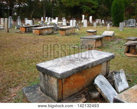 Old cemetery with stone caskets above ground.