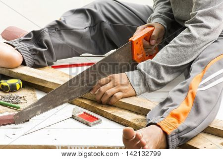 Male carpenter sawing wood.at work place.Background craftsman tool.