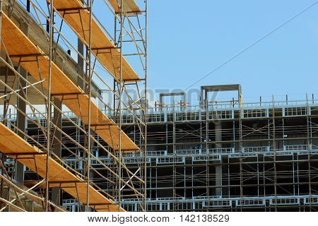 Construction site scaffolding wood and metal with blue sky background for copy space.