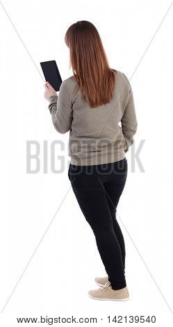 back view of standing young beautiful  woman  using a mobile phone. girl  watching. Rear view people collection.  backside view of person.  Isolated over white background. Thrusting his hand into the