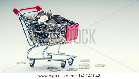 Shopping trolley. Shopping cart. Shopping trolley full of euro money - coins - currency. Symbolic example of spending money in shops or advantageous purchase in the shopping center.