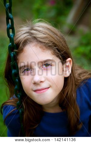 A confident and content tween girl sits on a swing resting her head against the rubberized chain. She looks at the camera with a close mouthed smile.