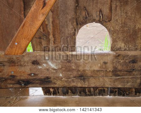 Closeup abstract of wooden door craftsmanship with rustic features and arched cutout.