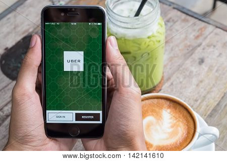 CHIANG MAITHAILAND - JUL 72016 : A MAN hand holding Uber app showing on iphone 6s. Uber is smartphone app-based transportation network