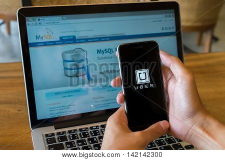 CHIANG MAITHAILAND - Aug 42016 : A MAN hand holding Uber app showing on iphone 6s or 6s Plus background Mysql in laptop. Uber is smartphone app-based transportation network