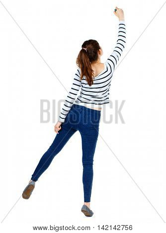 back view of writing beautiful woman. Rear view people collection.  backside view of person. Isolated over white background. Girl in a striped sweater standing on tiptoes and draws marker.