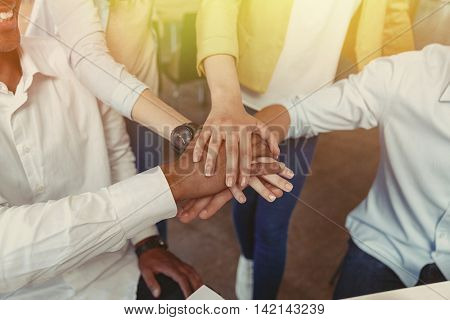 Closeup of multiethnic group of young people standing and joining hands poster